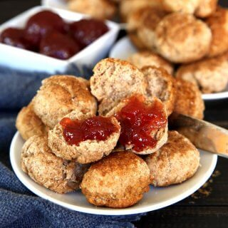 "Cinnamon Cookie Biscuits are 2"" across and are piled high on a white plate. Sitting on a navy cloth strawberry jam is waiting in a white square condiment bowl."