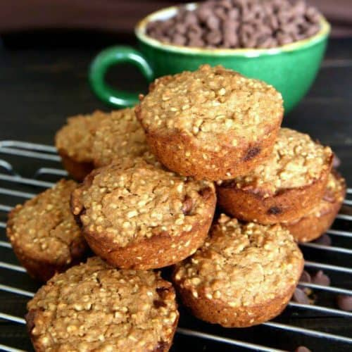 Irish Oatmeal Chocolate Chip Muffins are stacked high on their cooling rack with chocolate chips sprinkled around.