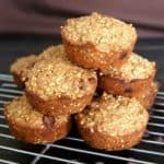 Irish Oatmeal Chocolate Chip Muffins stacked in a casual pyramid with golden color and on the cooling rack.