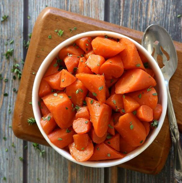 Maple Braised Carrots are cut at opposite angles and then are glistening in a buttery maple glaze. Served in a white bowl with a pierces serving spoon sitting alongside.