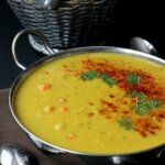 Red Lentil Dahl Soup is in a wide silver bowl with loop handles/ The rich yellow soup has red paprika and fresh green herbs sprinkled in an arc.