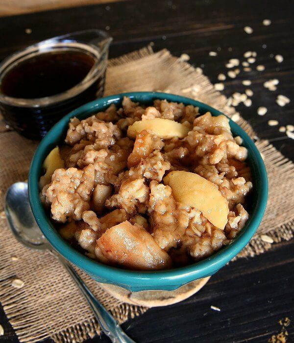 Slow Cooker Apple Oatmeal is piled into a turquoise bowl and tilted to keep the maple syrup in.