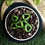 Slow Cooker Cuban Black Beans Recipe as an overhead shot with black beans in a white dish surrounded by black and green with jalapeño sliced rings on top.