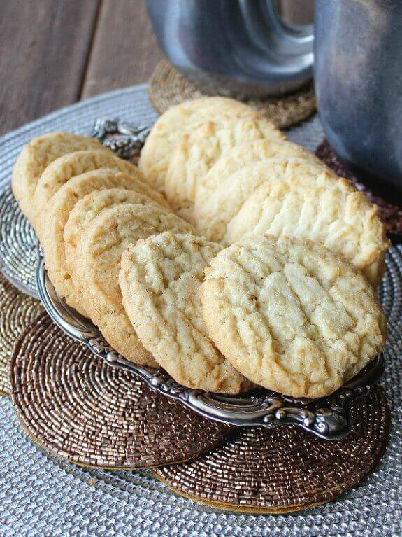 Almond Sugar Cookies are golden and are fanned out on a silver tray. Sitting in front of two pewter mugs.