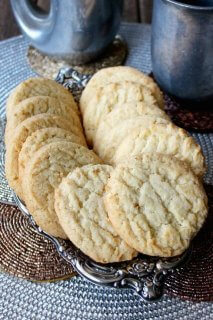 Almond Sugar Cookies fanned out on a silver tray and sitting golden on top of metallic colored rounds.