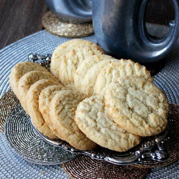 Almond Sugar Cookies fanned out on a silver tray and sitting golden on top of copper, brass and silver rounds.