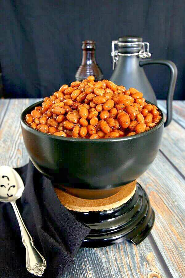 BBQ Baked Beans in their rust red color and piled high in a black bowl with a slotted spoon siting aside. Contrasting wood table in grays and rusty brown.