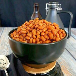 BBQ Baked Beans in their rust red color and piled high in a black bowl and sitting on a black trivet. Contrasting wood table in grays and rusty brown.