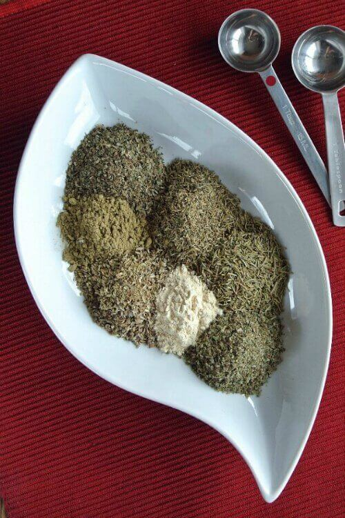 Homemade Italian Seasoning is in a white curved dish. All of the individual herbs are separated and waiting to be mixed.