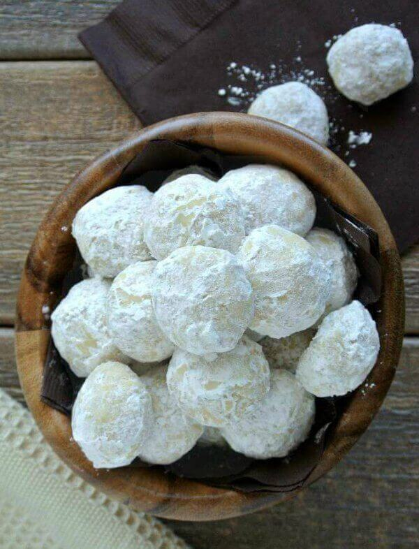 Mexican Wedding Cookies are covered with powdered sugar and being looked at from overhead. In a small dark wooden bowl.