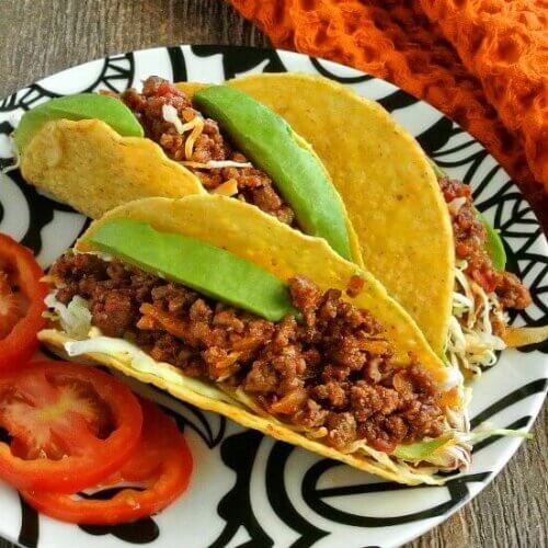 Mexican Sloppy Joe Tacos are three to a plate and tilted forward temping you with a lucious filling with bright green avocados are shredded slaw.