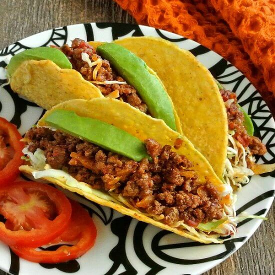 Mexican Sloppy Joe Tacos are three to a plate and tilited forward temping you with a lucious filling with bright green avocados are shredded slaw.
