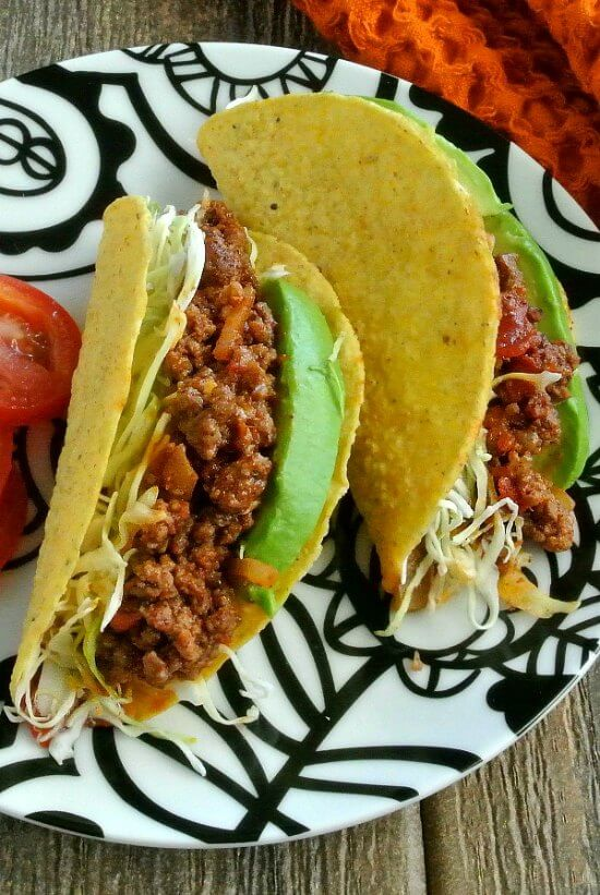 Mexican Sloppy Joe Tacos are three to a plate and oiled full of filling with bright green avocados are shredded slaw.