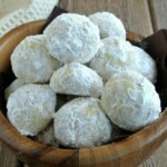 Mexican Wedding Cookies are covered with powdered sugar and are filling a small undulating wooden bowl.
