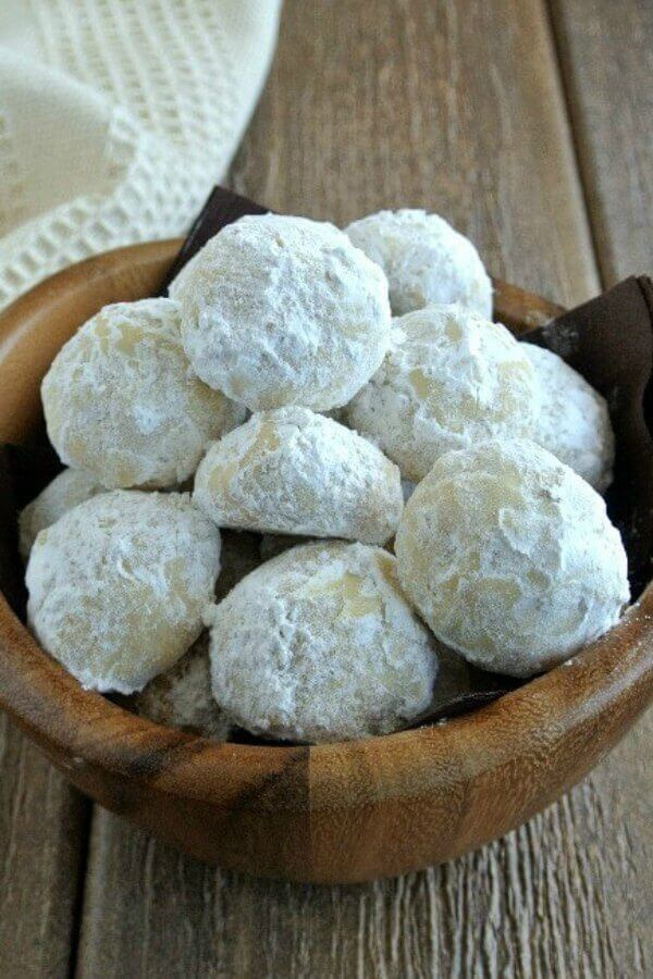 Mexican Wedding Cookies Are Covered With Powdered Sugar And Filling A Small Undulating Wooden Bowl