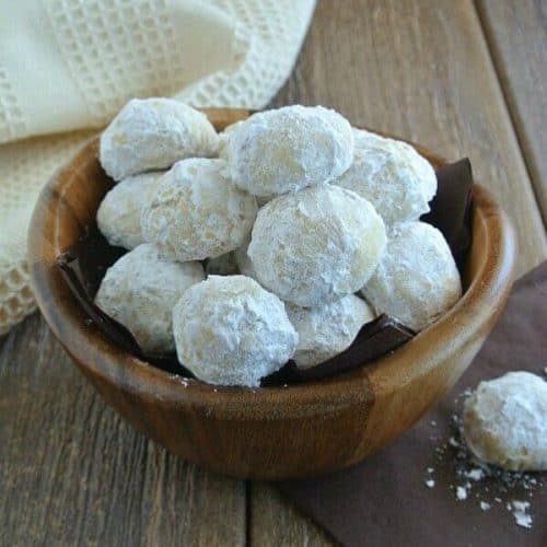 Treats covered with powdered sugar and are spilling over out of their brown wooden bowl and onto chocolate napkins.