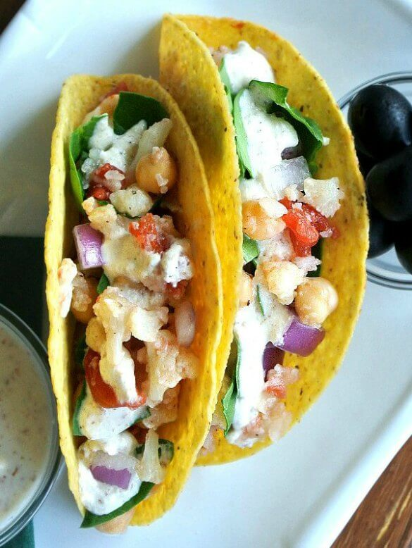 Ranch Cauliflower Tacos with an overhead view of corn tortillas filled with chunks of veggies and ladled with homemade vegan ranch dressing. Sitting on a white rectangular plate flanked with black olives and more ranch dressing.