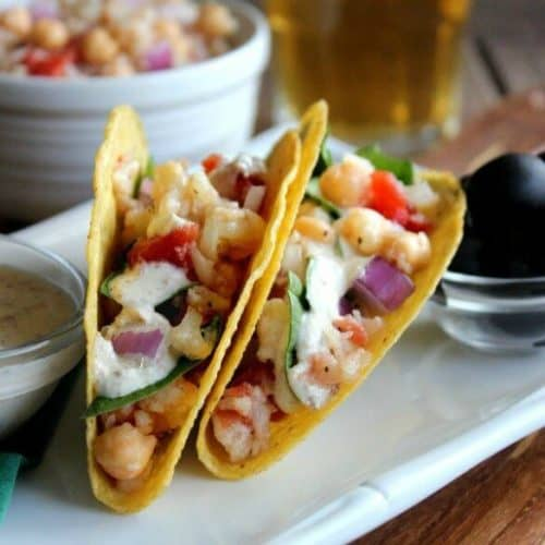 Ranch Cauliflower Tacos are angled toward the camera so there's a great view of corn tortillas filled with chunks of veggies. Homemade Ranch Dressing is spooned over it all.