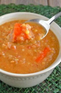 Slow Cooker Red Lentil Soup is o close-up of the rich orange soup in a white bowl. A spoon is holding a big bite up to you, front and center.
