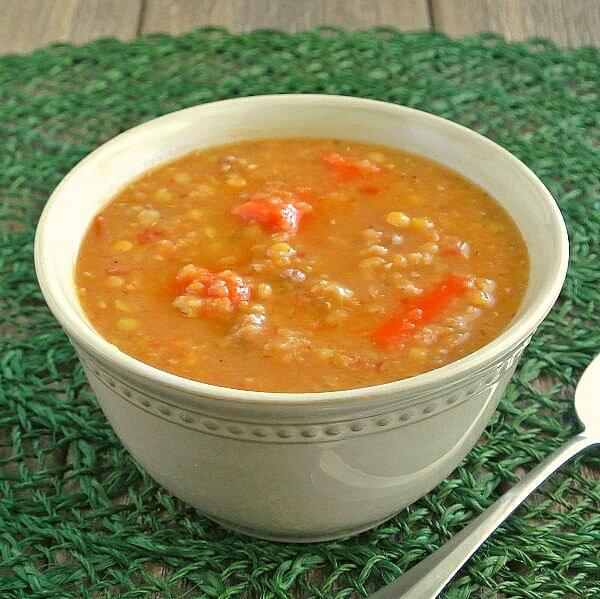 Rich Red Lentil Soup is in an ivory bowl on a green woven mat.