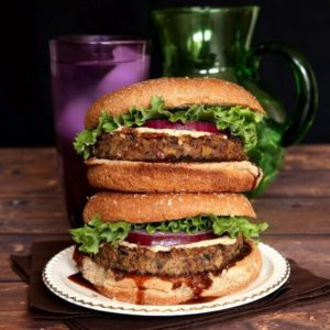 Vegan Mushroom Pecan Burgers are stacked double high with layers of curly lettuce, red onion and dripping hoison sauce.