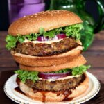 Vegan Mushroom Pecan Burgers are stacked double high and oozing with hoison sauce and big fat patties