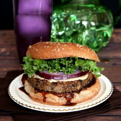 Vegan Mushroom Pecan Burgers are are oozing with hoison sauce with bright layers of curly lettuce and red onion.