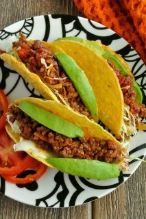 Mexican Sloppy Joe Tacos are three to a plate. Bright filling with bright green avocados are piled high.