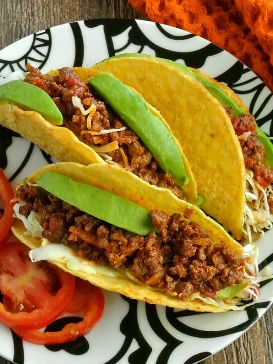 Mexican Sloppy Joe Tacos are three to a plate and piled high with filling with bright green avocados are shredded slaw.