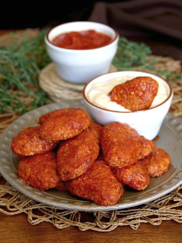 Boneless BBQ Buffalo Wings are baked in a red hot sauce and then piled high on a rustic beige plate sitting on an open weave straw mat.