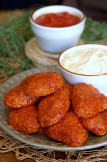 Boneless BBQ Buffalo Wings are baked in hot red and sweet sauce then piled high on a plate next to a creamy chipotle white sauce.