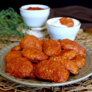 Boneless BBQ Buffalo Wings are piled high with a straight on photo with both white and red dipping sauce behind.