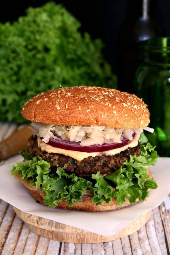 Crispy Anasazi Bean Burger made from dried beans is sitting in front of a beer bottle and a green drinking jar. The burger has green curly leaf lettuce, crispy brown burger and creamy colored sauerkraut finish the look.