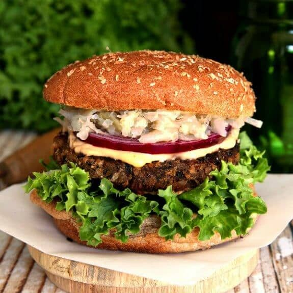 Crispy Anasazi Bean Burger made from dried beans is perfectly centered for the photo and has latyers of curly green lettuce, crispy brown burger, white sauce, red onion and sauerkraut. All is covered with a bun top.