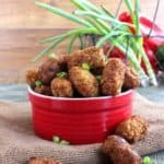 Vegan Chickpea Cauliflower Tots are crispy and golden brown. They are spilling over onto a brown cloth just waiting to be picked up and eaten.