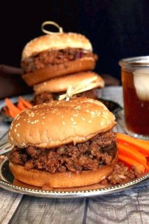 Vegan Sloppy Joes are overflowing with a spicy and tangy plant based filling rich in tangy mushrooms and onions. Bright orange carrot sticks are within reach.