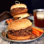 Vegan Sloppy Joes are stacked two high behind and one in front and all are perched on a silver tray. Bright carrot sticks are near at hand too.