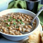 White Bean Chili is tilted forward with a spoon ladling the beans and broth up for a big bite.