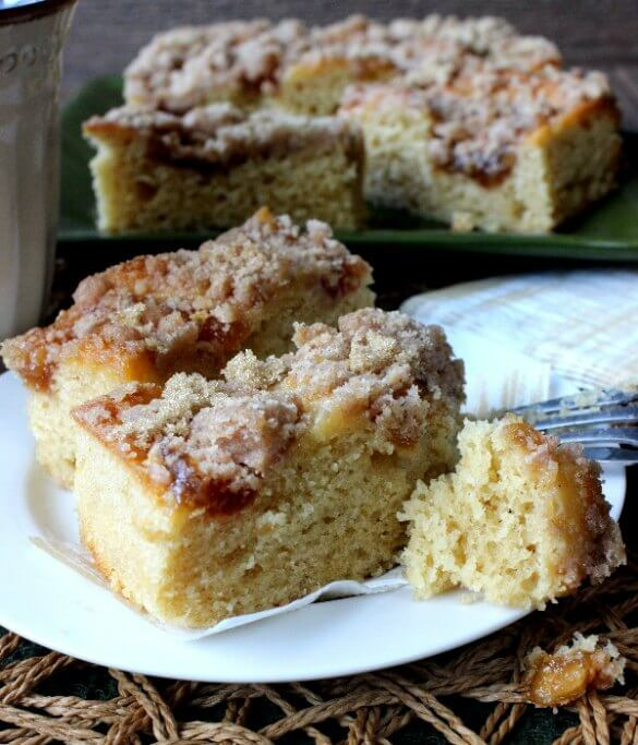 Vegan Coffee Cake with Apple Cinnamon Streusel is cut as two rectangles with a moist bite of cake sitting by a fork with a gold stripped napkin close at hand.