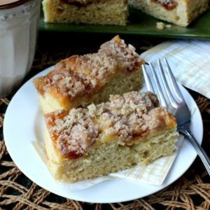 Vegan Coffee Cake with Apple Cinnamon Streusel is tilted forward with two slices sitting on a gold and white abstract patterned napkin and a white plate. A fork at the ready
