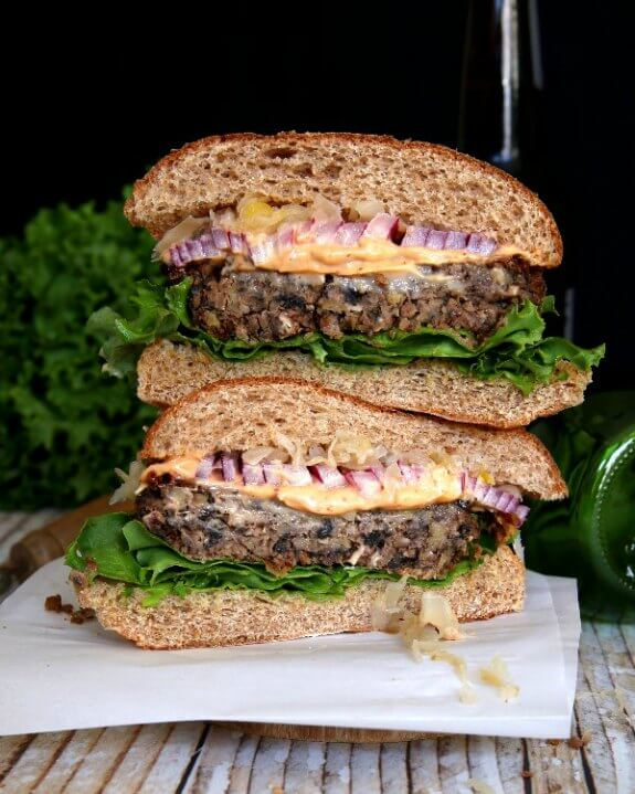 Crispy Anasazi Bean Burger have two halves stacked on top of each in this photo. Looking straight at the cross section of sliced patties, red onion and sauerkraut is begging for a bite.