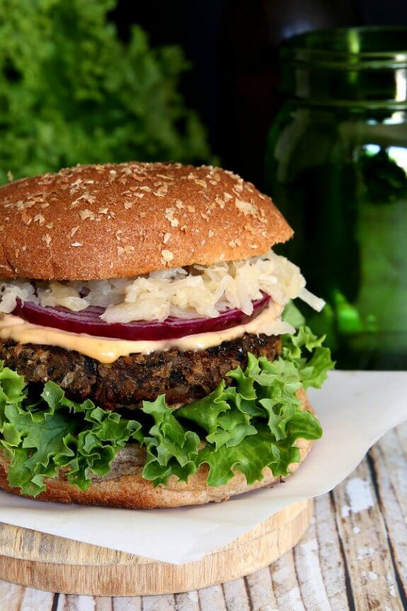 Crispy Anasazi Bean Burger is sitting on a square piece of parchment paper and the photo has cut the burger in half. green curly leaf lettuce, crispy brown burger and creamy colored sauerkraut finish the look.