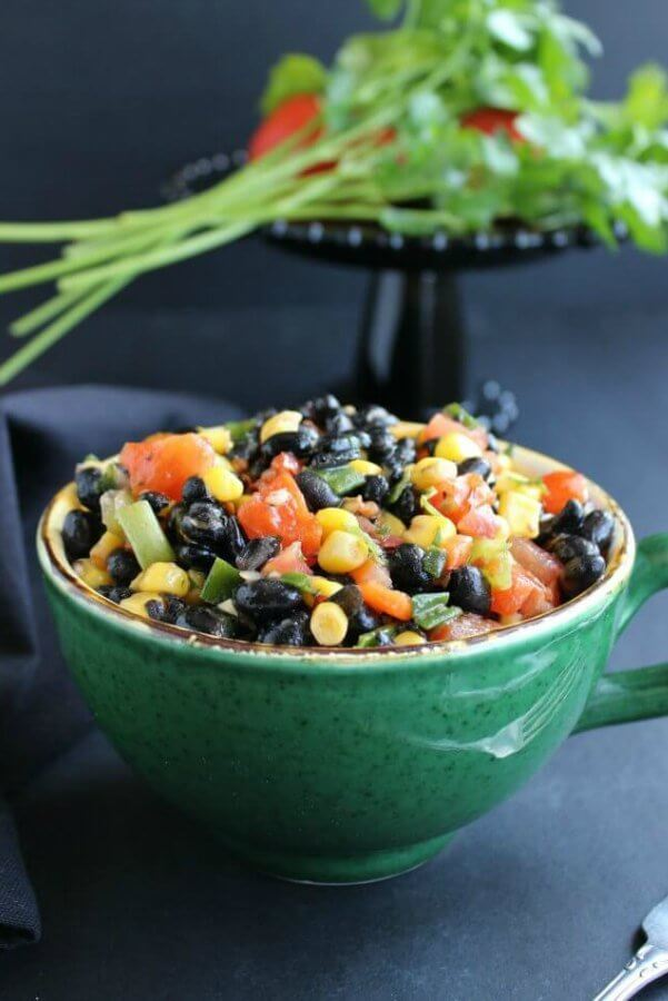 Fully Loaded Black Bean Salad is bright with yellow, black, orange and green and it's served in a giant green cup.