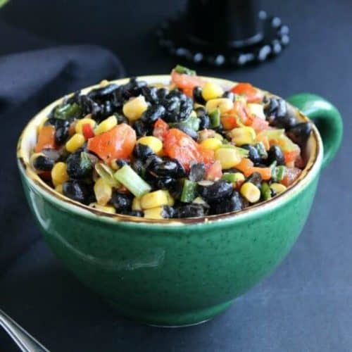Colorful veggies and beans fill a green bowl for no bake salad enjoyment.