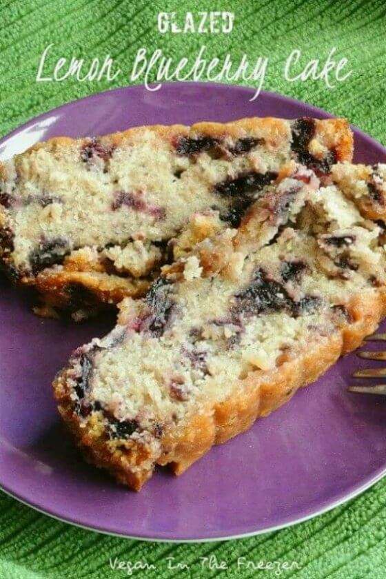 Glazed Lemon Blueberry Cake has two lovely moist slices on purple dish with a fork on the side.