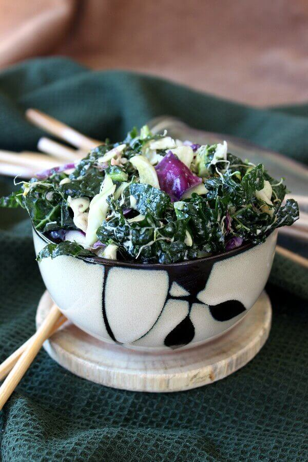 Massaged Kale Salad with Lemon Tahini Dressing is piled high in a bamboo designed bowl and shows green, white and purple veggies glistening with lemon tahini dressing. Chopsticks are waiting next to the bowl.