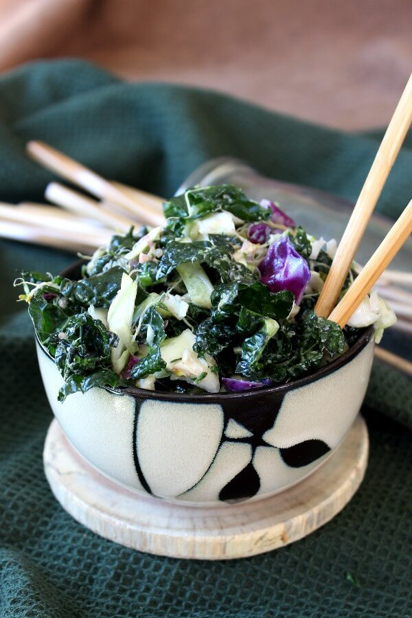 Massaged Kale Salad with Lemon Tahini Dressing is piled high in a bamboo designed bowl and has red cabbage popping out of the green alongside two chopsticks.