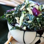 Massaged Kale Salad with Lemon Tahini Dressing is piled high in a bamboo designed bowl and shows green, white and purple veggies glistening with lemon tahini dressing.