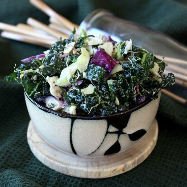 Massaged Kale Salad with Lemon Tahini Dressing is piled high in a bamboo designed bowl and tilted forward. Glistening tender greens, alfalfa shoots and contrasting purple and green cabbage is poking through.