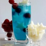 Patriotic Passion Cocktail is tall and blue with small white jicama stars and red raspberries floating inside.